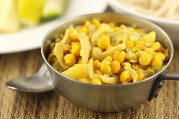 ひよこ豆をスプーンとサラダ野菜のボウルで調理