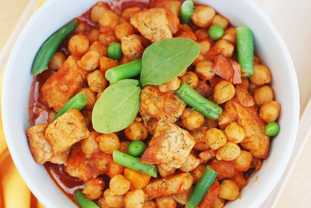 Cooked chickpeas with  meat and green beans. spanish traditional food.
