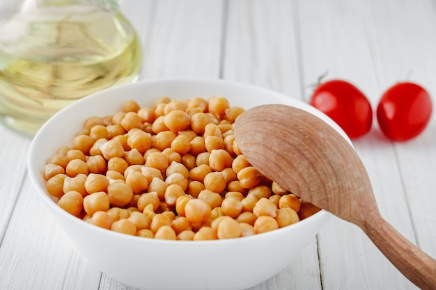 Cooked chickpeas with a plate, tomatoes and olive oil on a wooden table