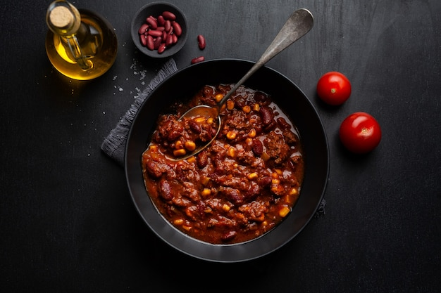 Cooked chili con carne served in bowl ready for eating on dark background.
