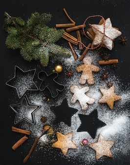 Cooked christmas holiday traditional gingerbread cookies with sugar powder, anise and cinnamon sticks on black