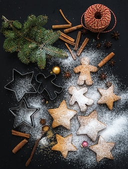 Cooked christmas holiday traditional gingerbread cookies with sugar powder, anise and cinnamon sticks