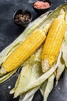 Cooked corn on cobs with salt and pepper. black background.