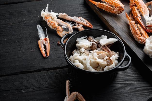 調理されたカニの爪と脚の肉セット、黒い木製のテーブル