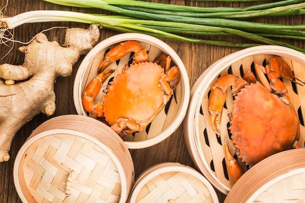 蒸し器と木製の板で調理されたカニ