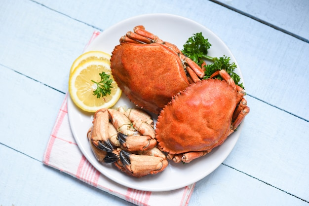 Cooked crab on white plate and wooden seafood boiled red stone crab claw with herb and spices