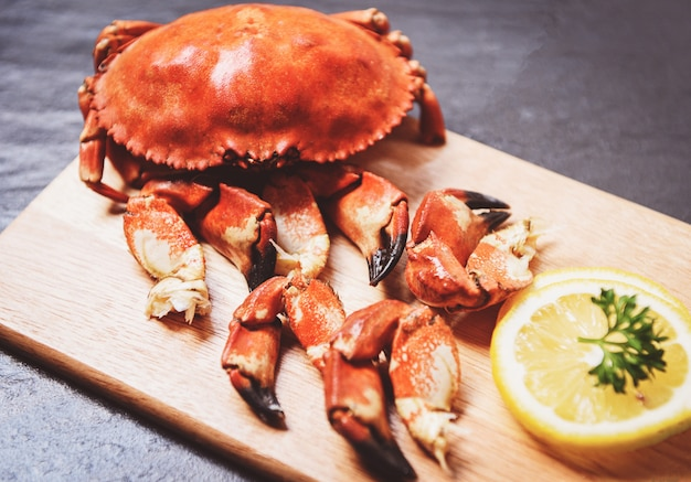 Cooked crabs boiled on wooden board with lemon on black plate