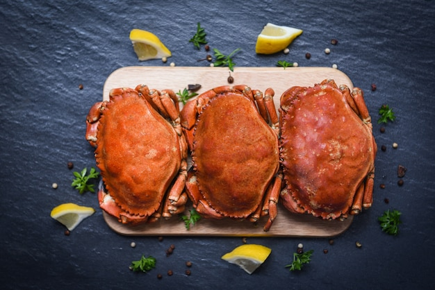 Cooked crabs on wooden board with lemon on plate served on dark plate