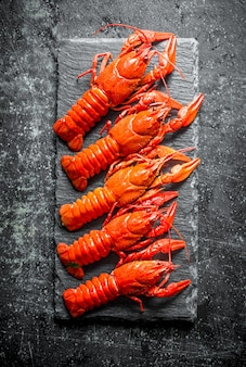 Cooked crayfish on a stone board on black rustic table