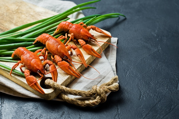 Cooked crayfish on a wooden chopping board.