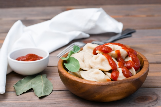 Cooked dumplings poured with ketchup with arugula leaves in a wooden bowl on a table