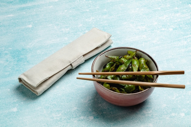 Cooked edamame on a blue tabletop. snack soybean pods
