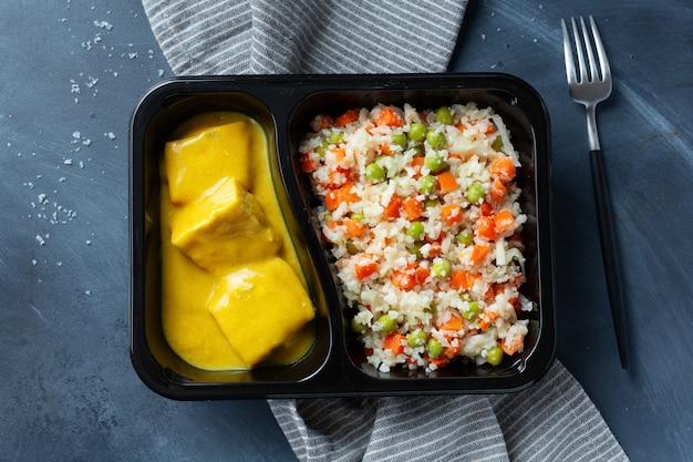 Bocconcini di pesce cotto con verdure crude e salsa al curry serviti in lunch box. avvicinamento.