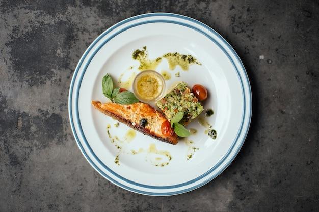 Un pesce cotto con salsa sui pomodori su un piatto bianco