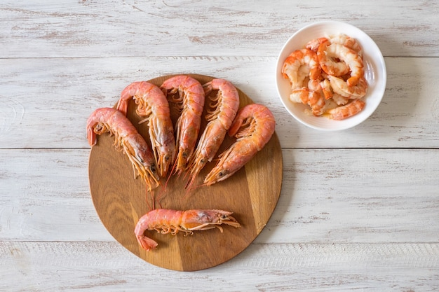 Cooked fresh giant prawns on a wooden chopping board. top view