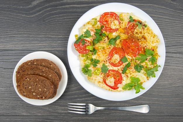 Приготовленный жареный омлет с зеленью и овощами в белой тарелке на деревянном столе