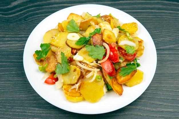 Приготовленный жареный картофель с зеленью и овощами в белой тарелке на деревянном столе