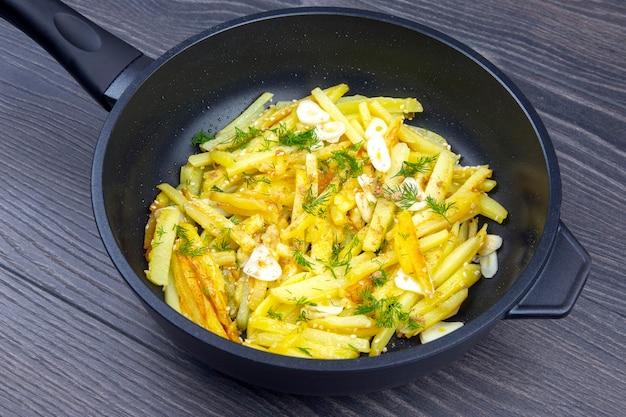 Приготовленный жареный картофель с зеленью, специями и овощами на черной сковороде на деревянном столе