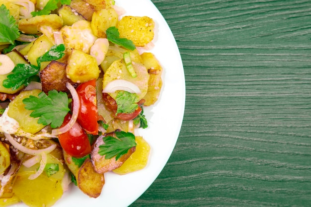 Cooked fried potatoes with herbs and vegetables in a white plate on a wooden table. copy space