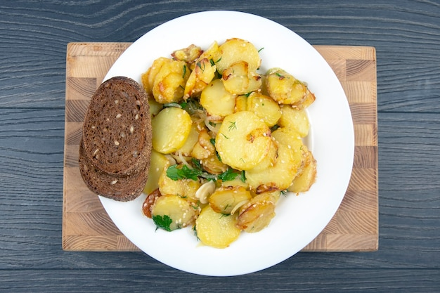 Cooked fried potatoes with herbs and vegetables in a white plate on a wooden table, top view