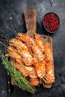 나무 판자에 그린란드 새우 새우 요리. 검정색 배경입니다. 평면도. 프리미엄 사진