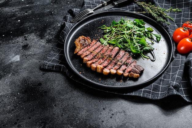 Приготовленный на гриле стейк из корейки, мраморная говядина с рукколой. черный фон