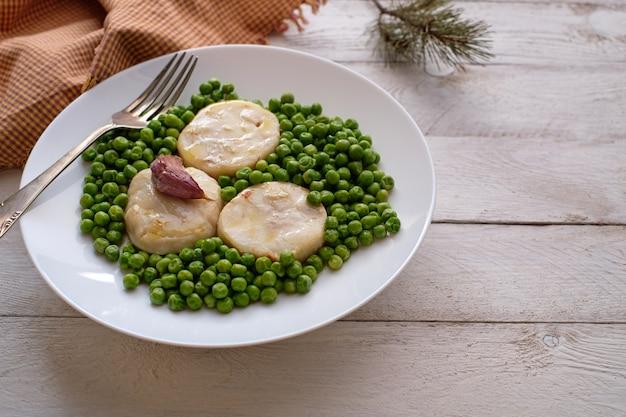 Приготовленные ломтики хека с горошком и чесноком на белой тарелке