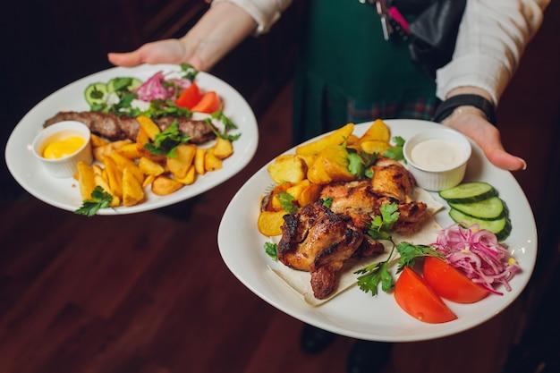 레스토랑 웨이터의 손에 접시에 야채와 함께 뜨거운 고기를 요리했습니다.