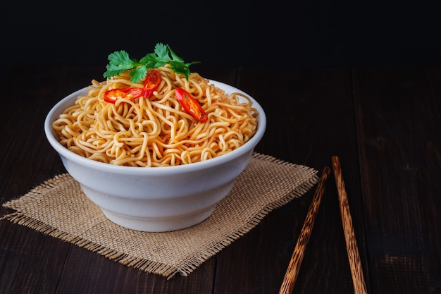 Cooked instant noodles in bowl with chopsticks close up on wooden table