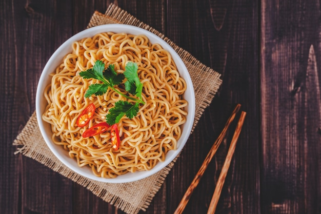 Cooked instant noodles in bowl with chopsticks in top view closeup on wooden table