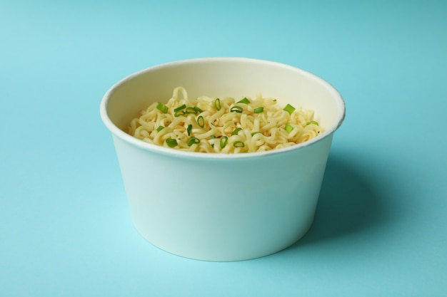 Cooked instant noodles in paper cup on blue