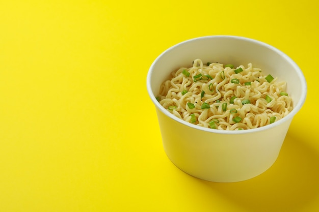 Cooked instant noodles in paper cup on yellow