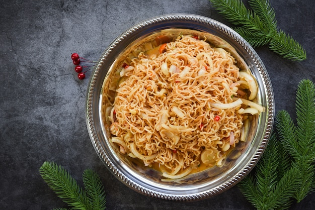 Cooked instant noodles on plate - noodle spicy salad with fir branches decoration festive food lunch festive christmas dinner
