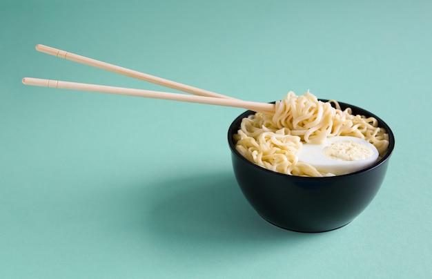 Приготовленная лапша быстрого приготовления с яйцом в черной пластиковой миске с палочками для еды на бумажном фоне