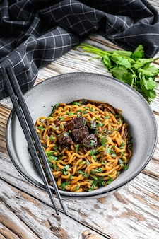 Cooked instant noodles with soy meat in a bowl. .