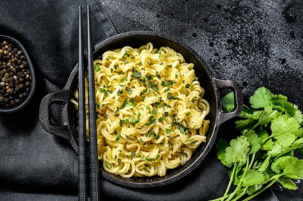 鍋に大豆肉を入れて即席めんを調理。ベジタリアン料理。黒の背景。上面図。
