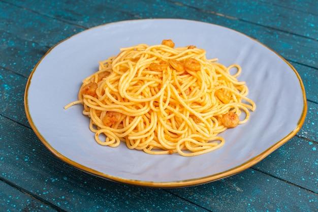 Приготовленная итальянская паста вкусная внутри ледяной тарелки на синем деревянном деревенском