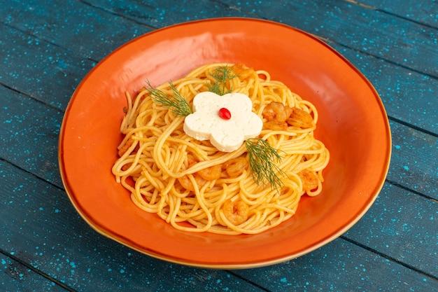 青い木のオレンジ色のプレート内の緑とイタリアのパスタおいしい食事を調理
