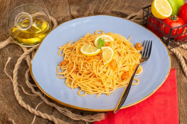 Приготовленная итальянская паста с зеленью и ломтиками лимона вместе с овощами и маслом внутри синего цвета