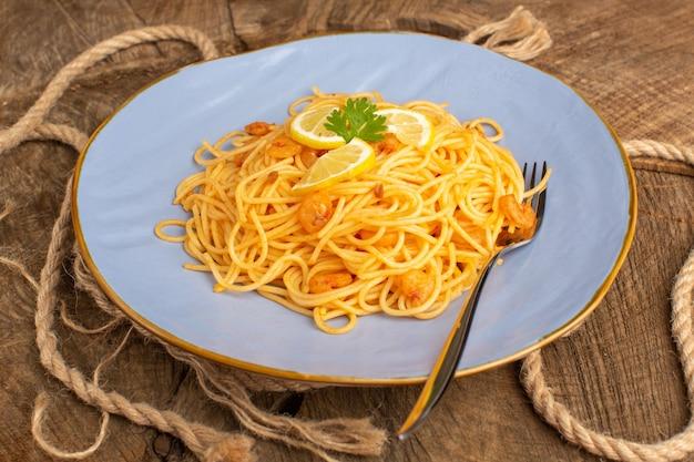 Приготовленная итальянская паста с зеленью внутри синей тарелки с веревками на дереве
