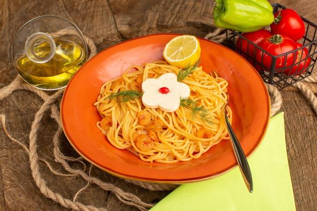 Pasta italiana cotta con verdure e fette di limone insieme a verdure e olio all'interno del piatto arancione su legno