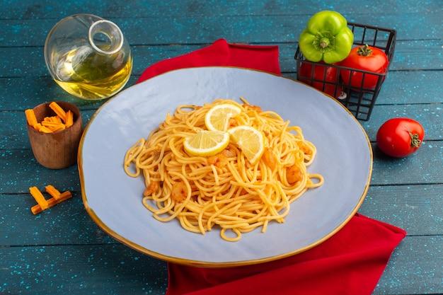 Приготовленная итальянская паста с ломтиками лимона на синей тарелке с маслом и овощами на синем