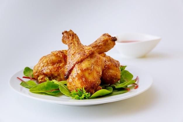 흰색 접시에 시금치와 닭 다리 요리