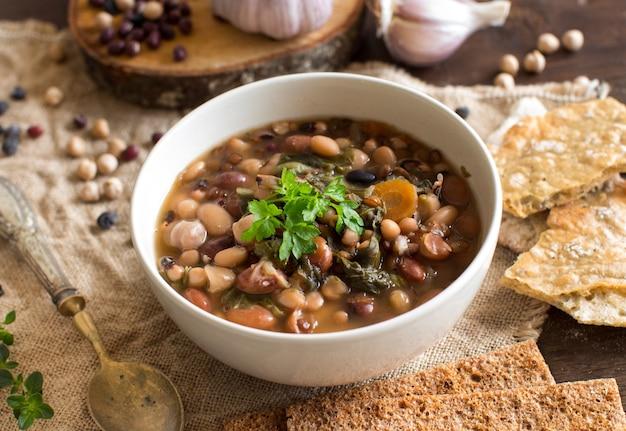 古い木製のテーブルのボウルで調理された豆類と野菜