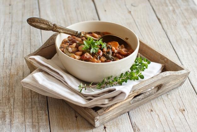 오래 된 나무 테이블에 그릇에 콩과 야채 요리