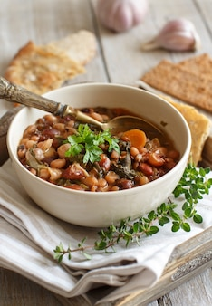 Cooked legumes and vegetables in a bowl on the old wooden table close up