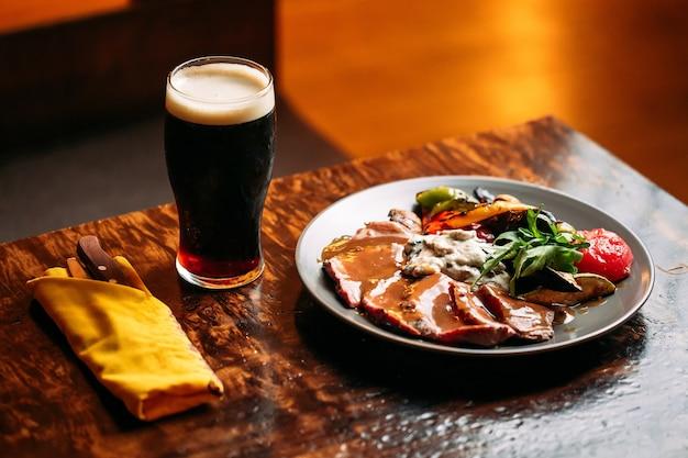 バーテーブルにダークドラフトビールのグラスと肉と野菜の料理