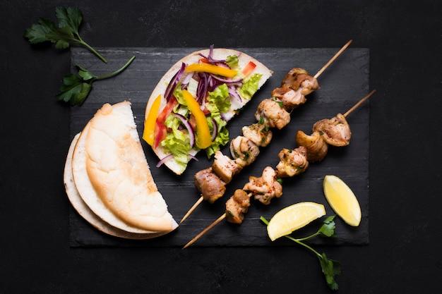 黒の背景に調理された肉と野菜のケバブ