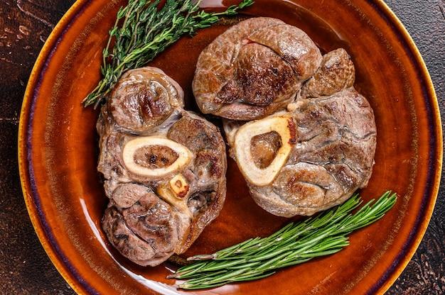 뼈에 구운 고기 osso buco 송아지 생크, 이탈리아 ossobuco 스테이크. 어두운 나무 배경입니다. 평면도.