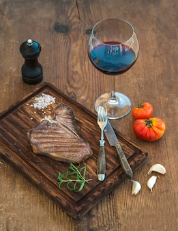 Cooked meat t-bone steak on serving board with garlic cloves, tomatoes, rosemary, spices and glass of red wine over rustic wooden  table